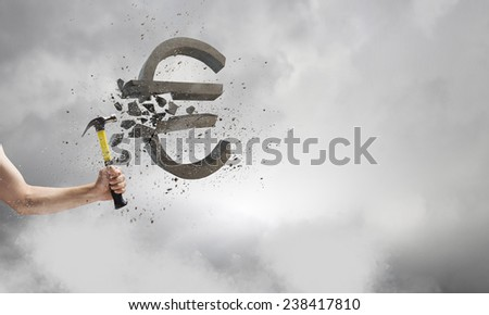 Close up of hammer in human hand breaking stone euro symbol - stock photo