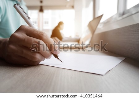 Close up of hand business man working with writing on white paper and laptop at workplace.