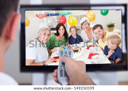 Close up of hand changing television channel through remote
