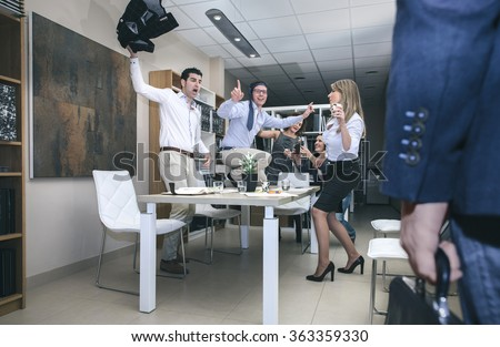 Close up of hand chief with briefcase arriving to office while his workers dancing and drinking in a big party - stock photo