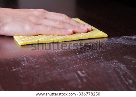 Close up of  hand cleaning wooden table with furniture polish. Using yellow sponge for cleaning dusty wood. House  cleaning and home hygiene concept - stock photo