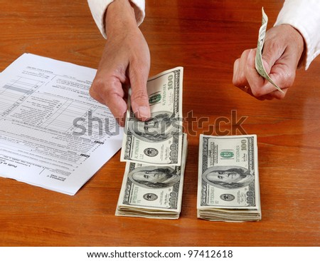 Close up of hand counting cash, near a  tax form - stock photo