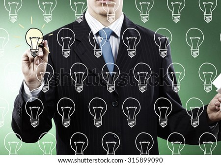 Close up of hand darwing light bulb with marker - stock photo