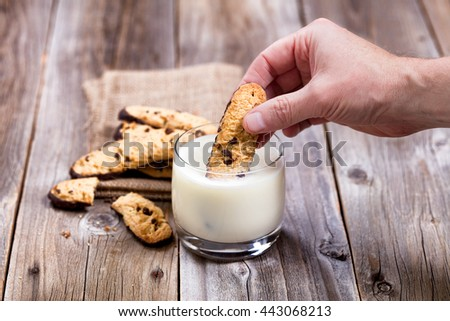 Close up of hand dipping chocolate chip cookie into glass of milk.
