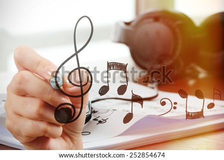 close up of Hand drawing musical notes on screen as music composer concept - stock photo