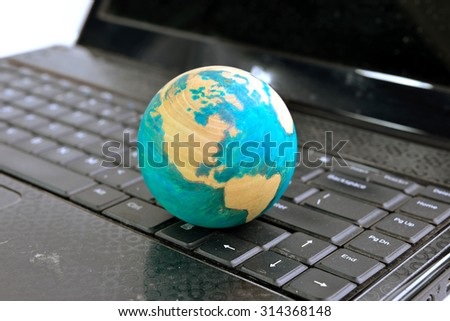 Close up of hand drawn globe isolated on computer keyboard, selective focus.