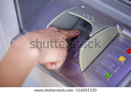 Close up of hand entering pin at an ATM. Finger about to press a pin code on a pad. Security code on an Automated Teller Machine. Female arms, ATM - entering pin