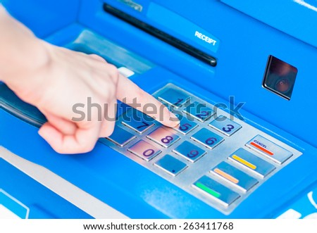 Close-up of hand entering PIN/pass code on blue ATM/bank machine keypad - stock photo