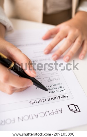 Close-up of hand filling application form - stock photo