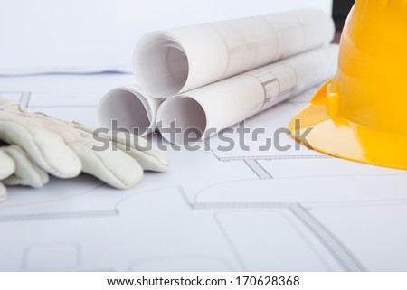 Close-up Of Hand Gloves With Hardhat On Blue Print - stock photo