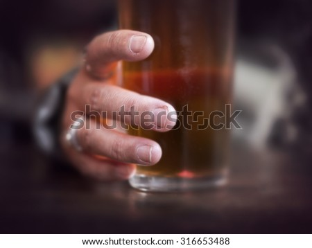 Close up of hand grabbing glass of beer in pub or bar - stock photo