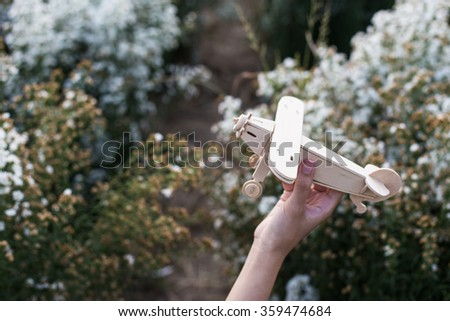 close-up of Hand holding a wooden airplane plane on white flower. - stock photo