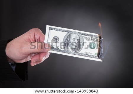 Close-up Of Hand Holding Burning Banknote Over Black Background - stock photo