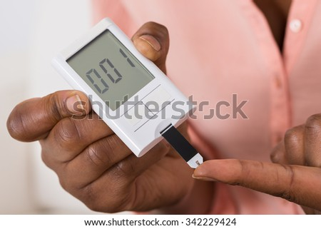 Close-up Of Hand Holding Device For Measuring Blood Sugar - stock photo
