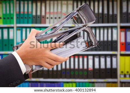 close up of hand holding file binder on office shelves - stock photo