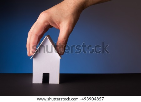 close up of hand holding house model, blue background.
