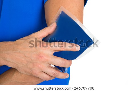 Close-up Of Hand Holding Ice Gel Pack On Elbow - stock photo