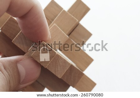 close up of hand holding padlock icon on cubic wood puzzle as internet security online business concept - stock photo