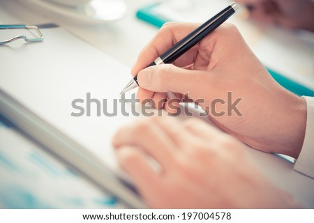 Close-up of hand holding pen - stock photo