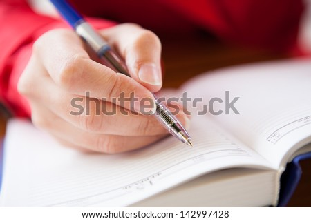 Close-up  of hand holding pen and writing in diary of hand writing in diary - stock photo