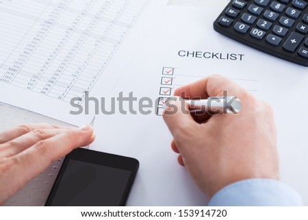 Close-up Of Hand Holding Pen Over Application Form With Mobile Phone And Calculator - stock photo