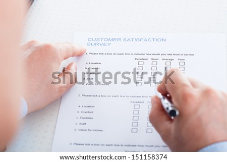 Close-up Of Hand Holding Pen Over Blank Check Box In Application Form - stock photo