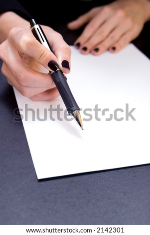 Close-up of hand holding pen pointing to blank document - stock photo