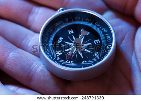 Close-up Of Hand Holding Silver Black Compass - stock photo