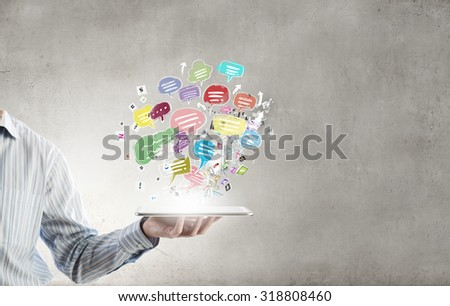 Close up of hand holding tablet pc with speech bubbles