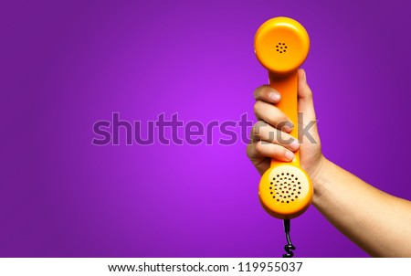 Close Up Of Hand Holding Telephone against a purple background