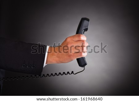 Close-up Of Hand Holding Telephone Receiver Over Black Background - stock photo