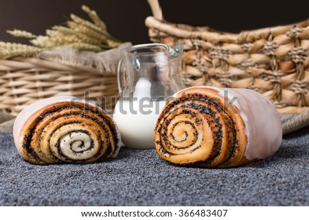 Close-up of hand made freshly baked sweet cinnamons with poppy seeds on rustic background with milk jug