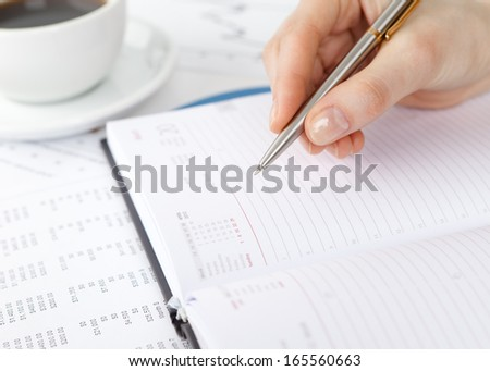 Close up of hand making notes in the notebook. Cup of coffee stands nearby