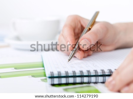 Close up of hand making notes in the writing pad lying on the diagrams - stock photo