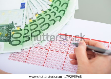 Close-up Of Hand Marking With Pen On Lottery Ticket And Banknote - stock photo