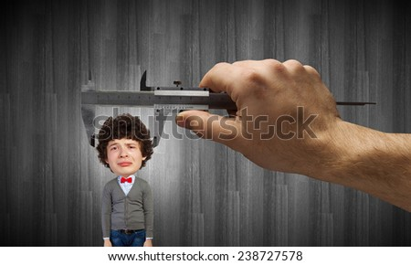 Close up of hand measuring head of guy with meter - stock photo