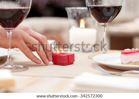 Close up of hand of a man giving a small box of gift to his girlfriend. They are sitting at the table in restaurant and drinking wine - stock photo