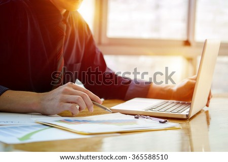 Close up of hand of business man working document and laptop in office morning light. - stock photo