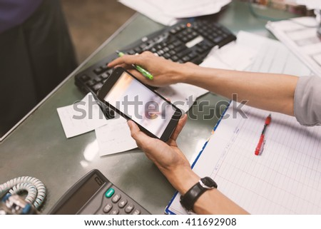 Close up of hand of business man working document and using mobile smart phone in office .