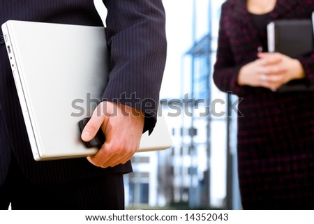 Close-up of hand of businessman holding laptop computer and mobile phone, businesswoman standing behind holding notebook.