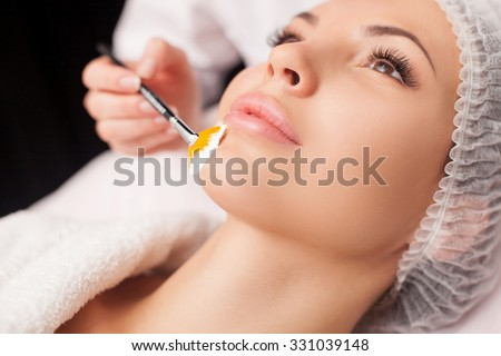 Close up of hand of cosmetologist applying cream mask on female face. She is holding brush. The beautiful young woman is lying with relaxation - stock photo