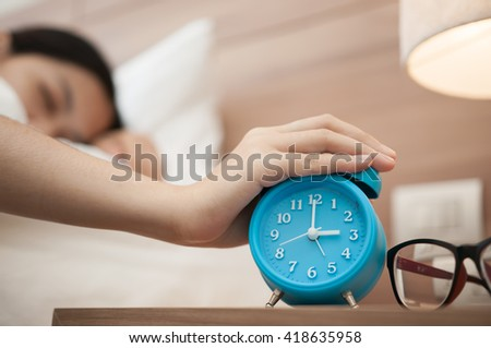 Close up of hand of girl turns off the alarm clock waking up in the morning. - stock photo