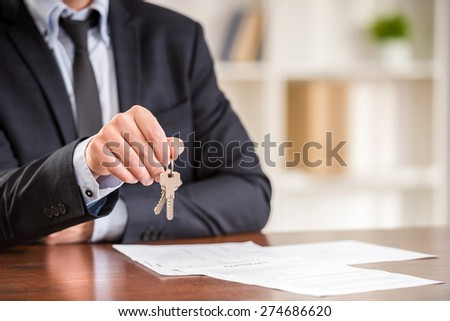 Close-up of hand of man is holding a key from a new apartment. - stock photo
