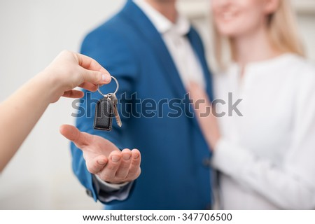 Close up of hand of realtor giving a key of apartment to married couple. The man and woman are standing and embracing. They are smiling. Focus on key - stock photo