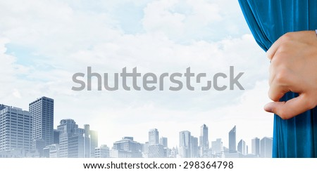 Close up of hand opening blue curtain. Place for text - stock photo