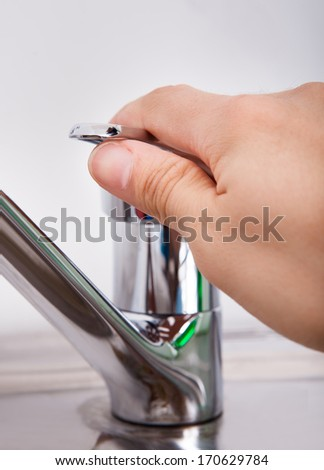 Close-up Of Hand Opening Chrome Water Tap  - stock photo