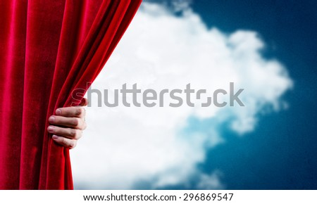 Close up of hand opening red curtain. Place for text