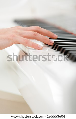 Close up of hand playing piano. Concept of music and art - stock photo