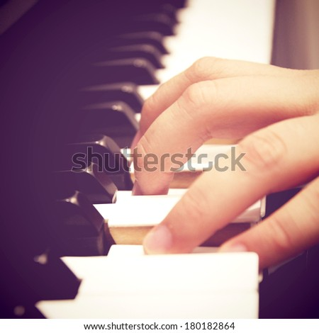 Close up of hand playing piano with retro filter effect - stock photo