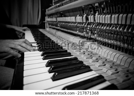 Close-up of hand playing the piano - stock photo
